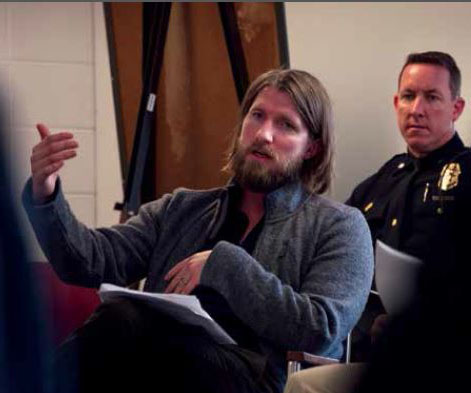 Brad Ray sits in a classroom with a police man behind him.