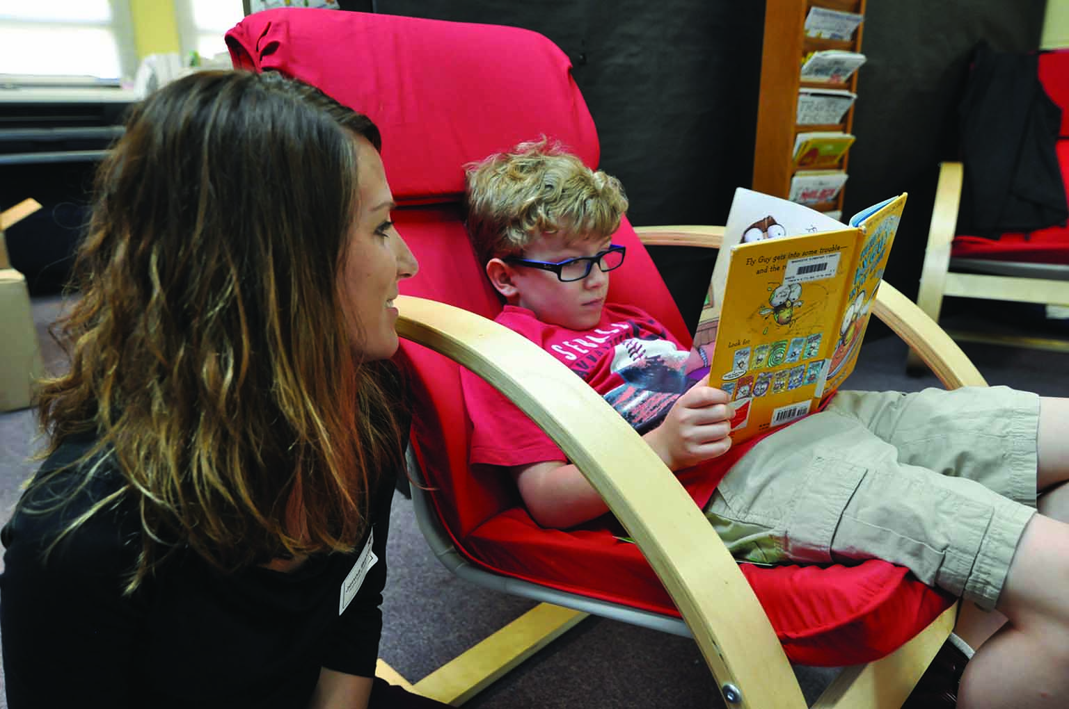 A little boy sits in a red chair and reads a picture book to a woman