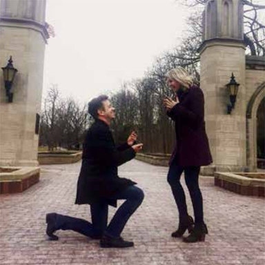 man proposes to woman in front of sample gates